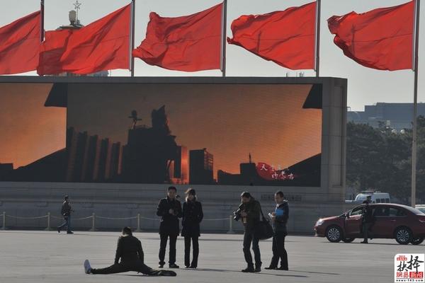 3月11日,全国两会召开期间,北京天安门广场红旗飘飘,一名男子表演劈腿秀。