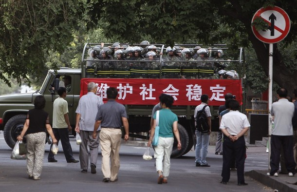 Chinese soldiers onboard a truck travel along a main street leading to the end of the city occupied by ethnic Uighurs in Urumqi