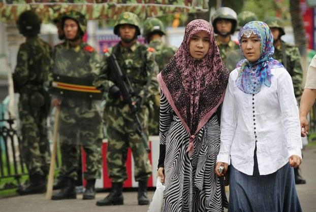 资料图片:2009年7月14日的新疆乌鲁木齐,两名维族妇女身后的街道上有军警持枪巡逻。(法新社)