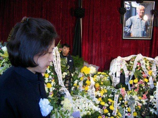 图片: 2005年1月19日,赵紫阳的女儿王雁南在摆满花圈的灵堂前,向前来拜祭的访客致谢。 (法新社资料图片)