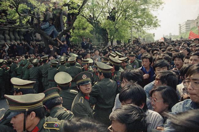 """1989年4月27日,为了反对《人民日报》的社论将学生运动斥为""""动乱"""",抗议者向天安门广场进发,试图突破警戒线时,与警方扭打起来。"""