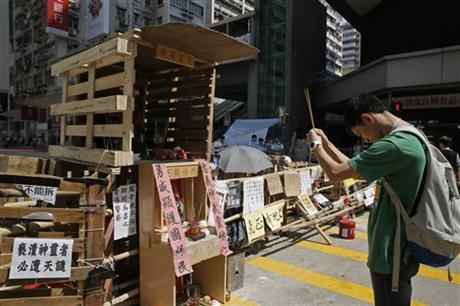 2014年10月11日周六,抗议者们设置的路障封锁了香港旺角的主要道路,一座供奉着中国民间英雄和关羽神的迷你庙宇安置在路障处,一名男子向其作揖祷告。在抗议者、警察和愤怒的暴徒间数个夜晚的打斗和暴力冲突后,这个庙宇是一种巧妙的回应。旺角是香港三合会或其他有组织犯罪团伙的所在地,而暴徒和警察都不想冒犯到关羽,他们都把其作为他们的守护神。庙宇两旁的中文意思是:「勇威顯護國保,忠義神武靈佑。」摄影:Vincent Yu/美联社