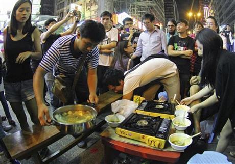 2014年10月9日周四,人们在香港旺角一处被封锁的主要道路上吃一顿火锅晚餐。警方迅速就一系列行为向抗议者们表示谴责,亲北京的报纸在头版发表照片。一名警察说,「非法占领者们将占据的道路作为了生活空间和游乐场。」摄影:苹果日报/美联社