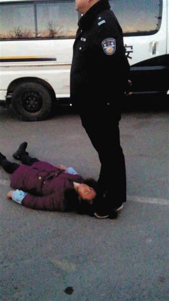 一名身穿警服的男子疑似用脚踩着周秀云的头发。新华社发
