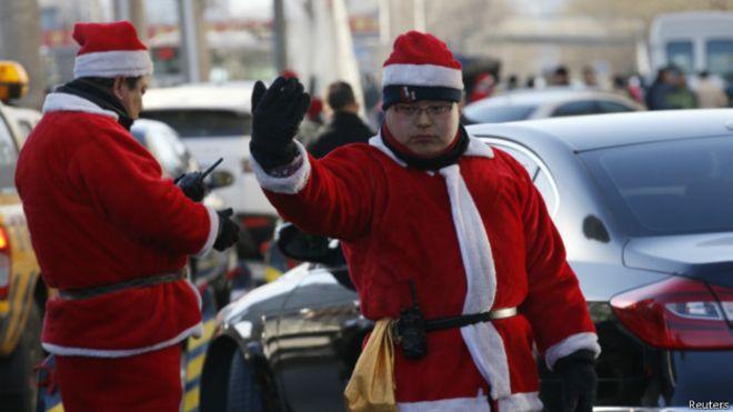 圣诞节当天,北京一家商场外的保安身穿圣诞老人服装在马路上帮助疏导交通。