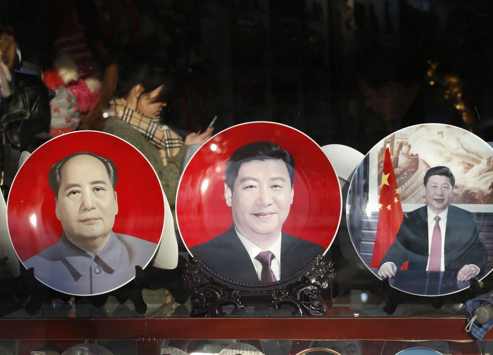Souvenir plates bearing images of China's President Xi Jinping and China's late Chairman Mao Zedong are displayed at a shop nearby Great Hall of the People where National People's Congress will be held, in Beijing