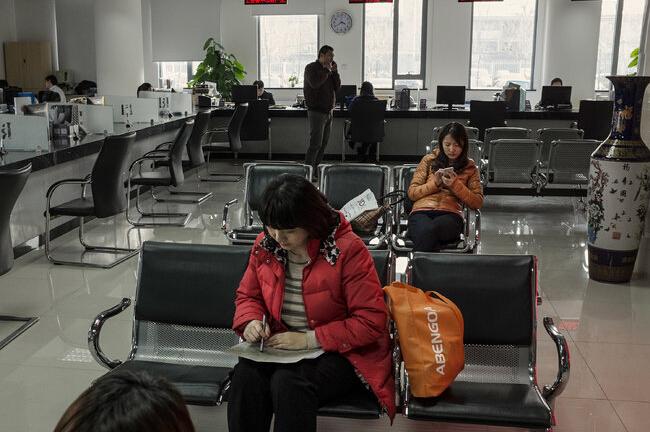 一家机构的等候大厅。包括李英(中)在内的外地来京人员来这里申请暂住证。需要有暂住证,她年幼的儿子才能入学。