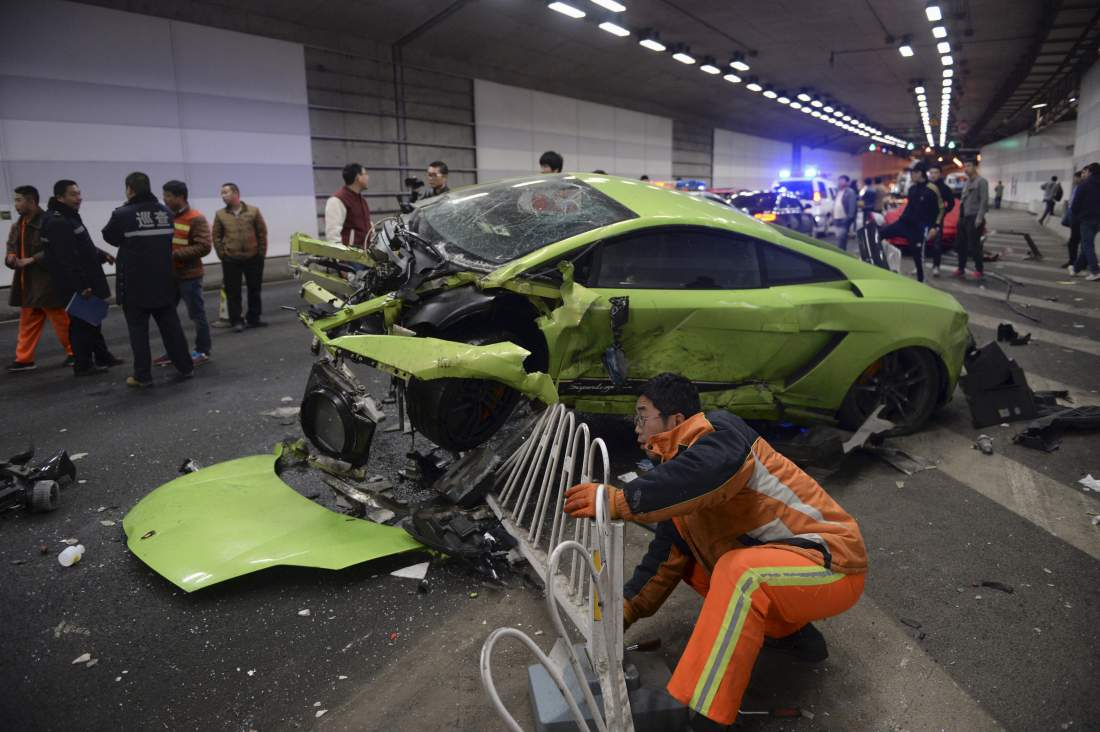 A rescuer tries to remove a part of a broken fence below a damaged Lamborghini after it collided with a Ferrari inside a tunnel in Beijing, April 12, 2015. One passenger was injured during the incident, while policemen are looking into the cause. Residents nearby said the tunnel is a common spot for illegal car racing in Beijing, local media reported. REUTERS/Stringer CHINA OUT. NO COMMERCIAL OR EDITORIAL SALES IN CHINA  TPX IMAGES OF THE DAY      - RTR4WZG0