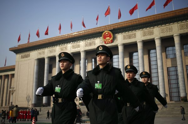 武警在中国立法机构所在的北京人民大会堂前行进。