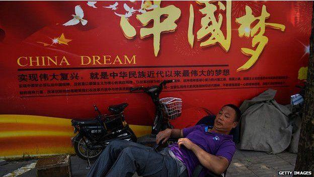 """男子躺卧在写着国家主席习近平喊出的""""中国梦""""的广告牌下,牌上写着""""实现伟大复兴,就是中华民族近代以来最伟大的梦想""""。"""