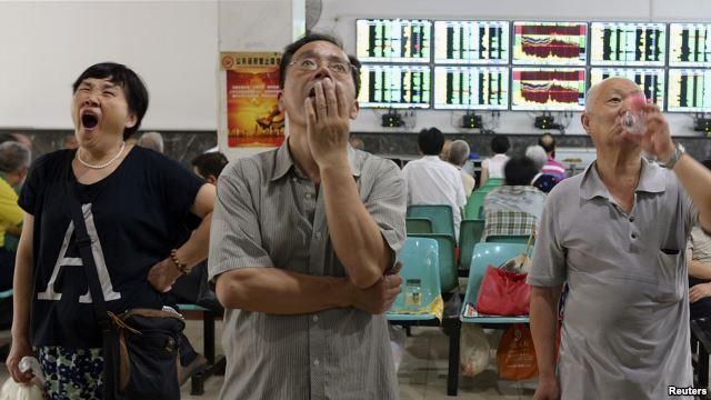 在武汉的证券交易市场,股民们看着电脑屏幕上的股市行情。