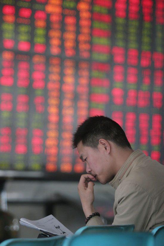 某证券营业厅里,一个年轻股民在琢磨大盘走势。