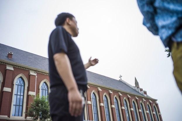 图片: 天津一天主教教堂的牧师在新建的教堂外接受采访,称感谢当局斥资1900万元兴建该教堂。 (法新社图片)