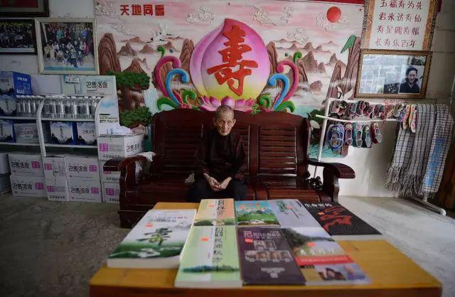 在广西巴马县坡月村,115岁的黄卜新老人是目前长寿村年龄最大的百岁老人,他坐在椅子上,周围摆满了销售品。图片来自腾讯新闻《图话》:广西巴马长寿村
