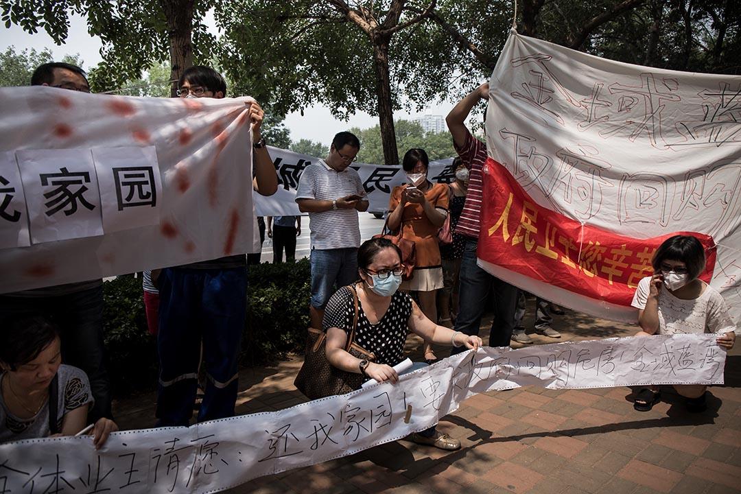 2015年8月17日,天津,爆炸現場附近的災區居民於飯店門外示威,要求政府回購及安排住屋安置。攝: Billy H.C. Kwok/ 端傳媒