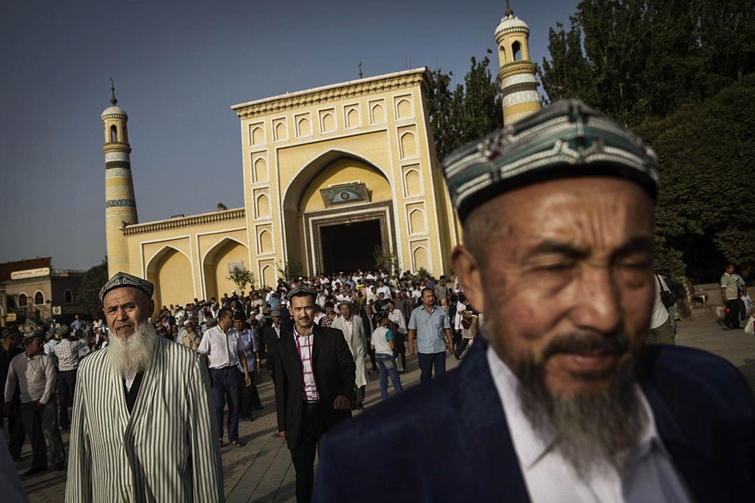 KASHGAR, CHINA - JULY 29: Uyghur men leave the Id Kah Mosque following the Eid prayers on July 29, 2014 in old Kashgar, Xinjiang Province, China. Nearly 100 people have been killed in unrest in the restive Xinjiang Province in the last week in what authorities say is terrorism but advocacy groups claim is a result of a government crackdown to silence opposition to its policies. China's Muslim Uyghur ethnic group faces cultural and religious restrictions by the Chinese government. Beijing says it is investing heavily in the Xinjiang region but Uyghurs are increasingly dissatisfied with the influx of Han Chinese and uneven economic development. (Photo by Kevin Frayer/Getty Images)