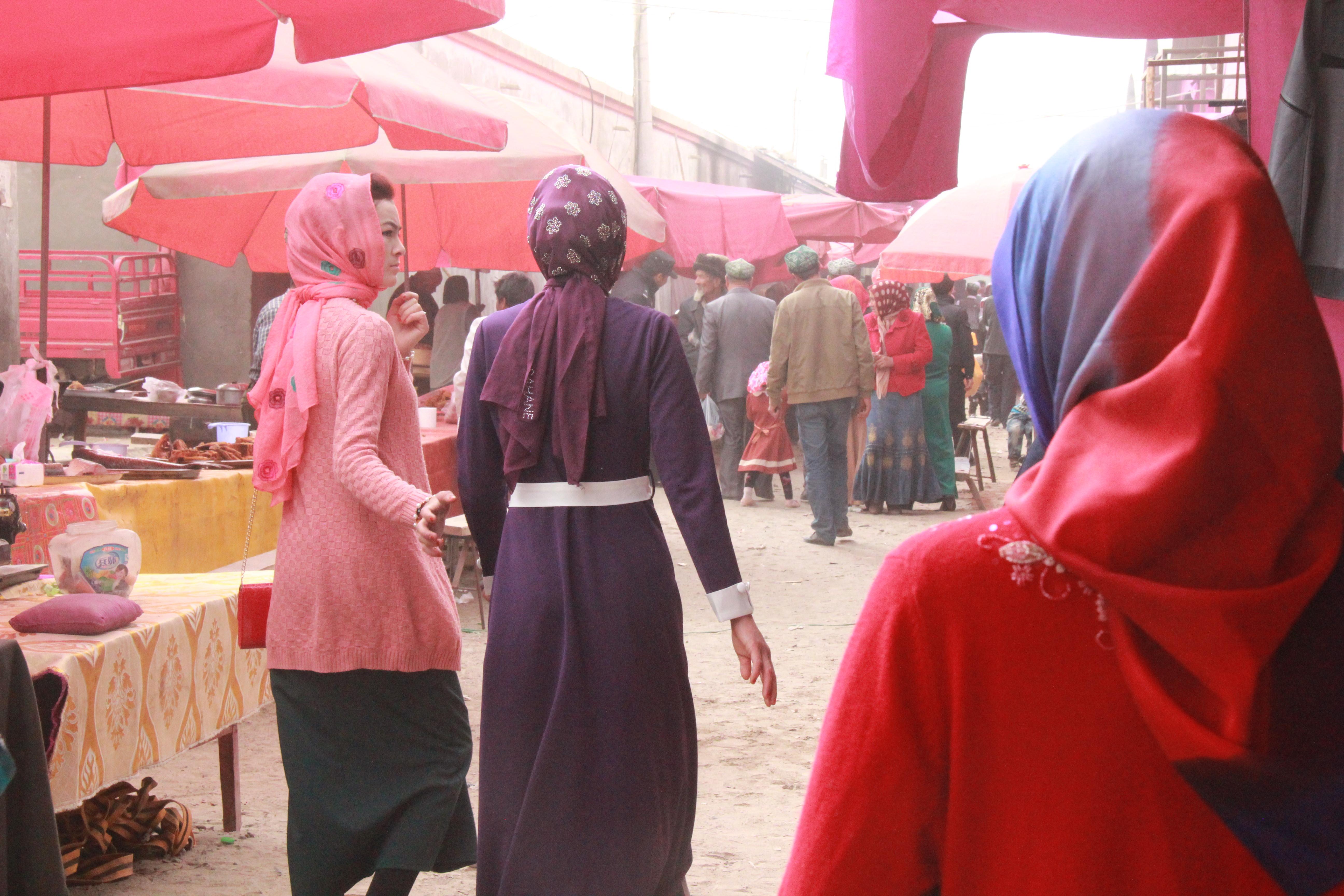和田地区墨玉县喀尔赛镇巴扎,两位穿着时尚的女子走过。和田地区曾是宗教极端思想渗透严重地区,当地官员称过去巴扎上随处可见穿戴蒙面罩袍的女子,如今街面上已见不到。摄影:陈芳