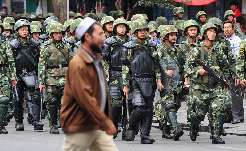 Armed Chinese soldiers march on patrol as a Uighur man crosses the street in Urumqi on July 15, 2009 in northwest China's Xinjiang province. Security remains tight in Urumqi's Muslim Uighur district 10 days after the worst ethnic violence China has seen in decades since unrest broke out on July 5 as riot police maintained their presence and kept control of the area's main bazaar, which they have commandeered as a base. AFP PHOTO/Frederic J. BROWN (Photo credit should read FREDERIC J. BROWN/AFP/Getty Images)