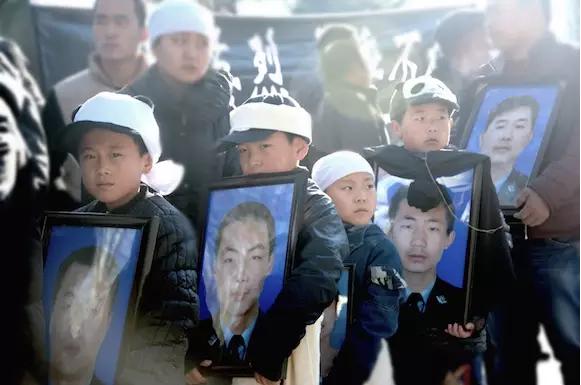 下葬当天,弟弟们抱着哥哥的遗像,右二为刘治强  (图:刘诗蕾/CFP)