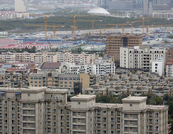 上月,中国天津的住宅楼和建筑工地。该市8月12日发生的工业爆炸导致173人死亡,附近很多房屋严重受损。