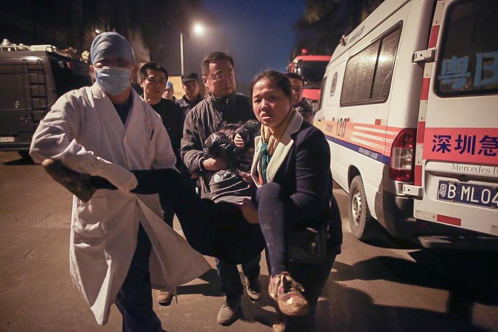 傍晚六时许,一名在灾区找寻失踪亲友的女家属因伤心过度而晕倒,由救护员扶往救护车治理。摄:端传媒摄影部