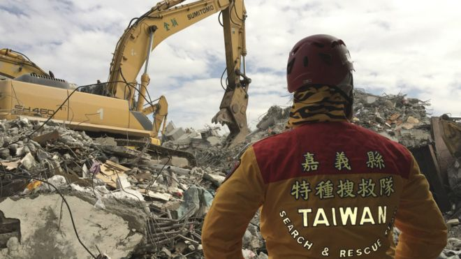 160213031033_a_member_of_rescue_teams_stands_by_as_heavy_excavation_machinery_continues_to_dig_through_the_rubble_of_a_collapsed_building_complex_in_tainan_taiwan_976x549_ap_nocredit