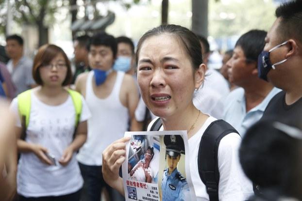 图片:2015年8月16日,一名失踪消防员的家属手举亲人照片出现在天津爆炸事故新闻发布会场外。(AFP PHOTO)