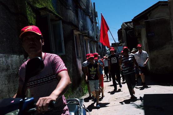 村民拿着国旗,沿村内小路走到举行村民大会场。摄:端传媒摄影部