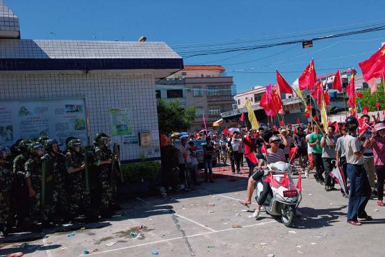 村民于村内游行,近村口处有百多名公安戒备,部份配备盾牌。摄:端传媒摄影部