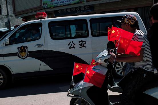 参与游行的村民乘着插满国旗的摩托车,驶经停泊于村口的公安车辆。摄:端传媒摄影部