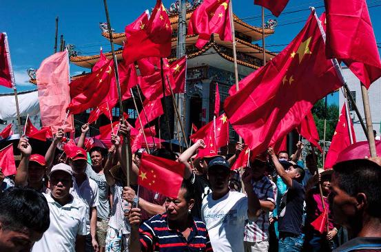 村民于华光庙外挥舞国旗,高叫口号。摄:端传媒摄影部