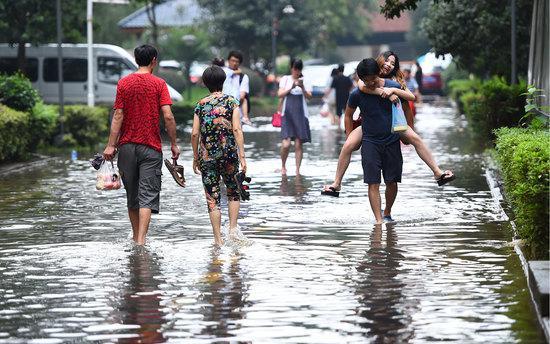 2016年07月03日,湖北省武汉市,南湖雅园小区,居民打赤脚、或让男朋友背出积水区。/视觉中国