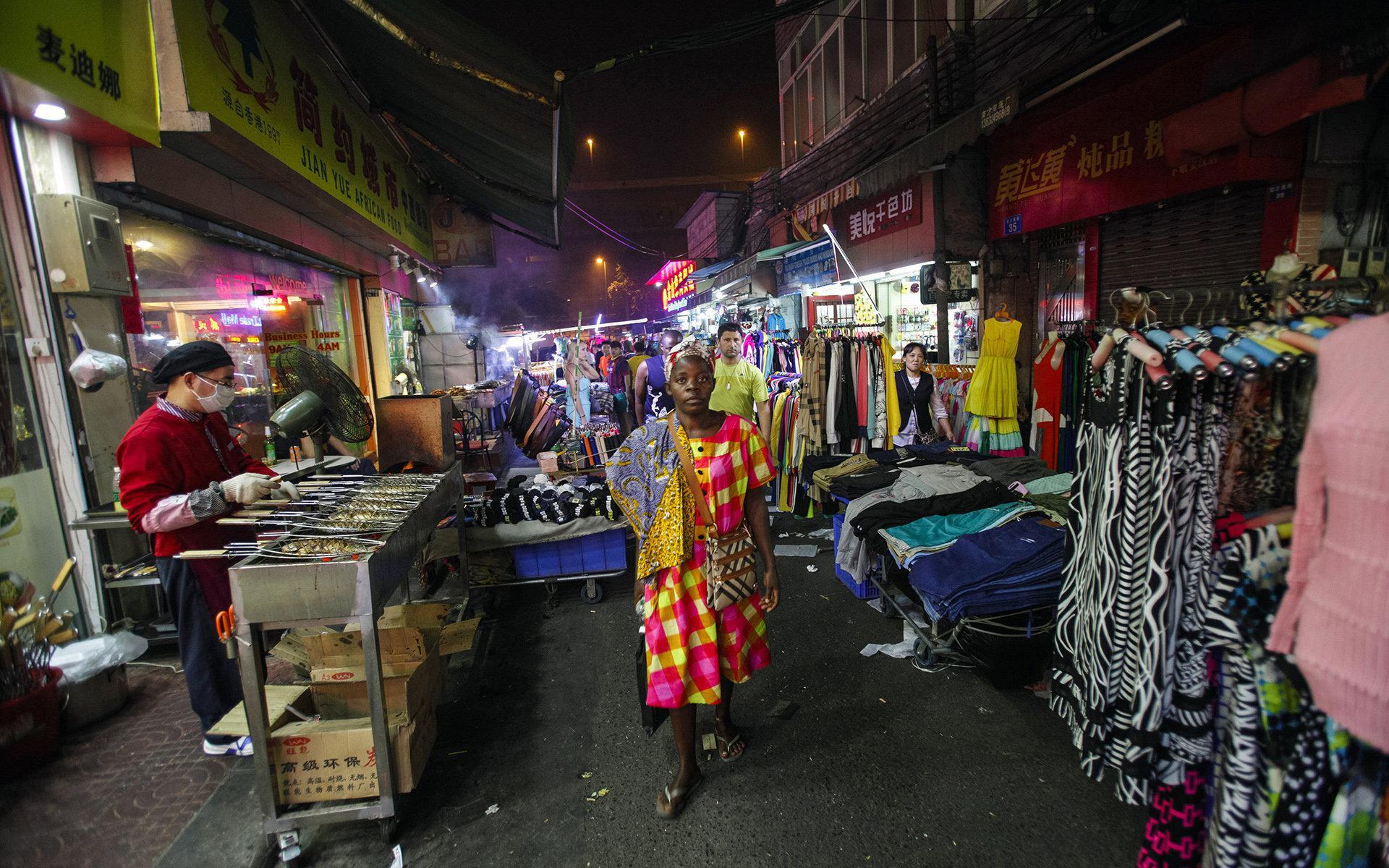 """2014年10月25日,一名非洲女人走在广州市的""""非洲村""""。/Reuters"""