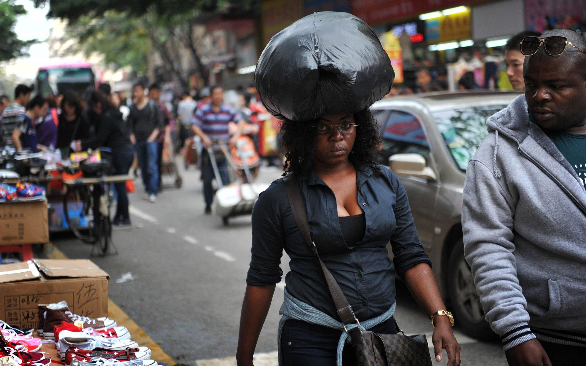 2014年4月3日,广州市一名黑人女子头顶刚挑选好的货品。/视觉中国