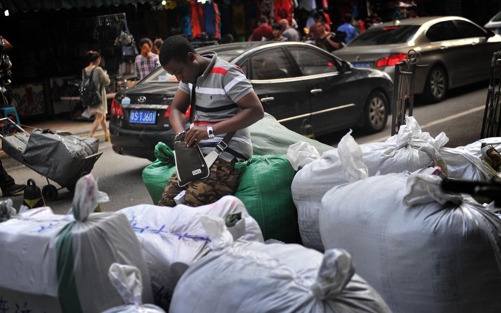 2014年4月3日,广州市一服装城旁一名拿到货的黑人男子在清点货品。/视觉中国