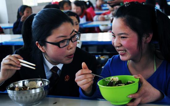 """2012年04月27日,重庆,工作人员在了解寄宿制学生的""""营养午餐""""。/视觉中国"""