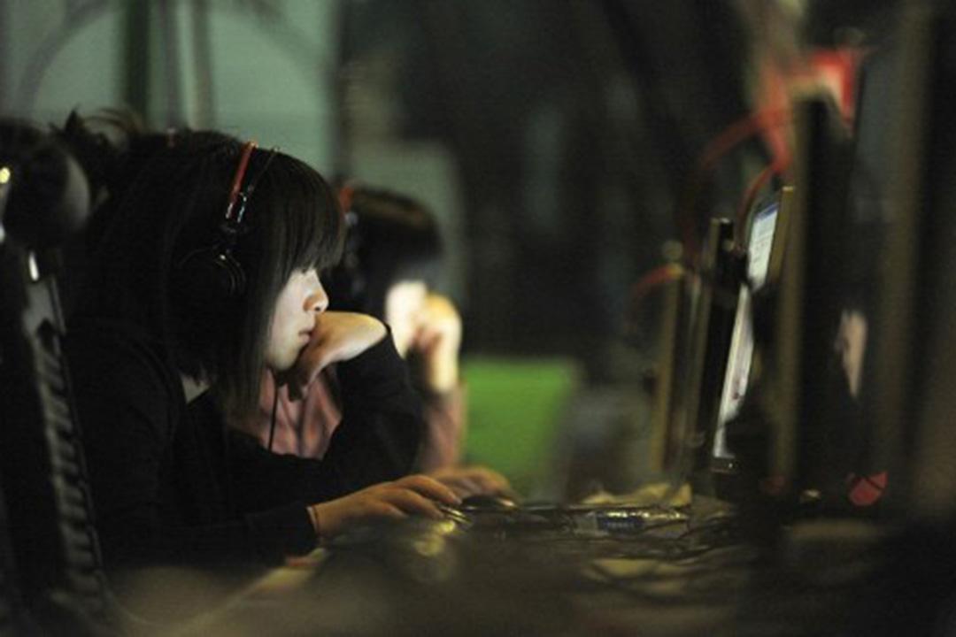 图为北京一名女子在网吧中使用电脑。摄:Gou Yige/AFP