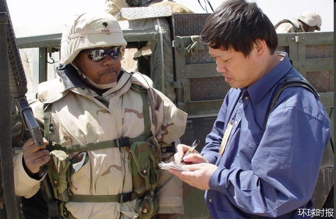 2003年伊拉克战争前夕,胡锡进在伊科边境采访美军士兵。