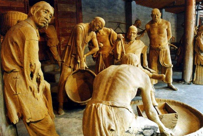"""真人大小的泥塑群雕""""收租院"""",展现刘文彩和他的""""狗腿子""""如何压榨贫农。"""