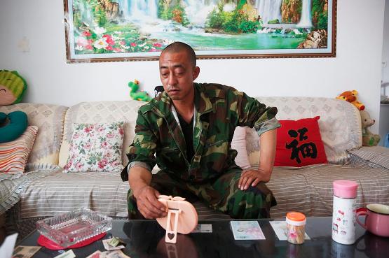 消防员杨伟光的父亲杨杰在一家人租住的平房里。摄:Howard/端传媒