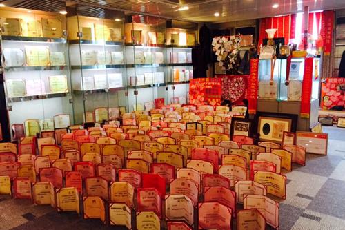 六楼的荣誉室的地面、墙面摆满了荣誉证书、锦旗和赠品。 图/财新记者 周淇隽