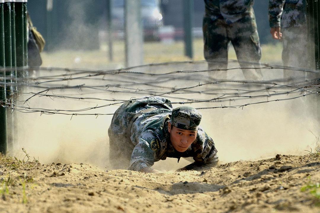 聊城大学国防生在进行匍匐过铁丝网项目训练