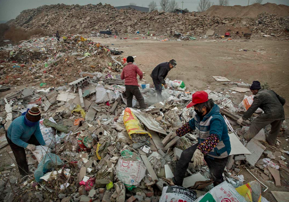 中国北京,工人们正在废品堆里搜索可回收品。废品回收种类繁多,曾经什么东西都可以卖钱。摄:Kevin Frayer/Getty Images