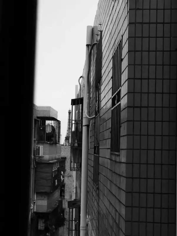 """从白石洲城中村的缝隙看到不远处世界之窗的""""巴黎铁塔""""。"""