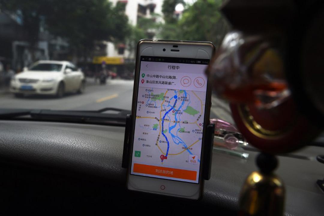 一名出租车司机在車上使用网约应用程式。摄:GREG BAKER / AFP