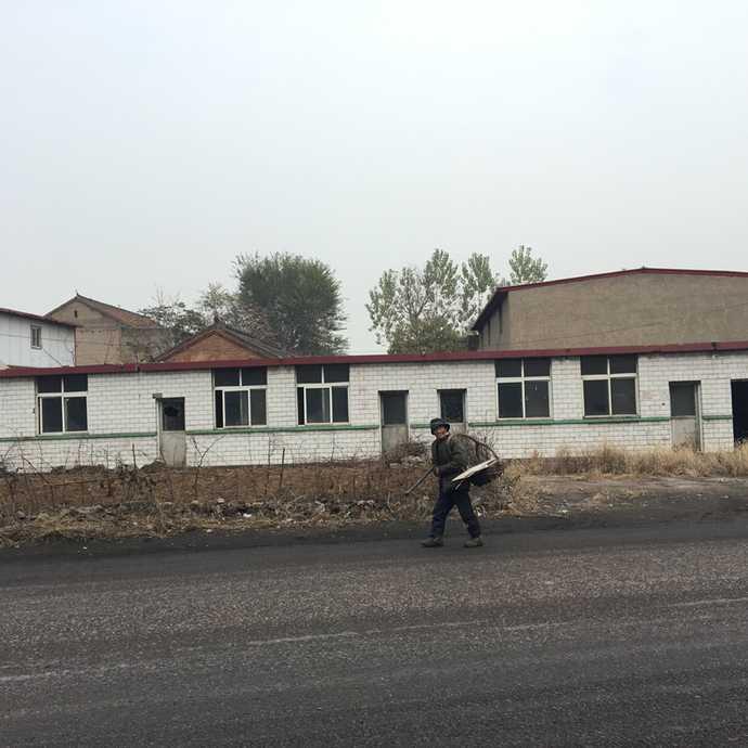 道路两旁废弃的院落,一位拾荒老人经过。摄|冯存健