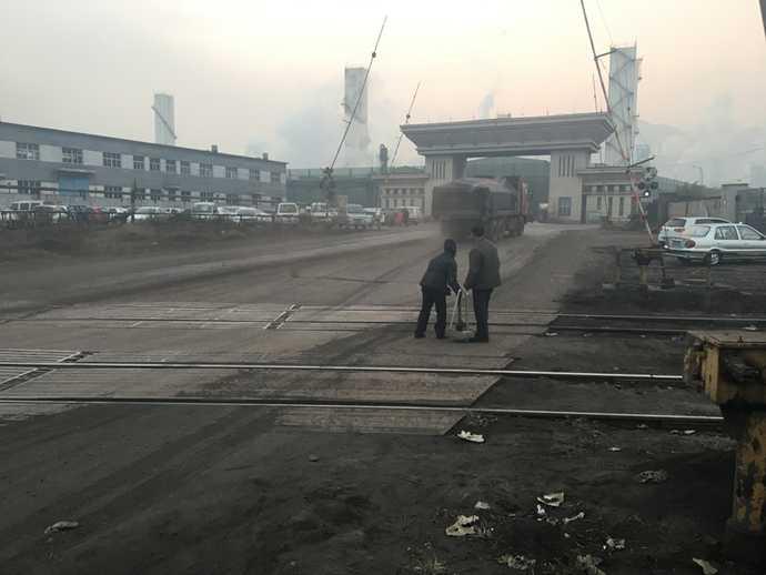 一对老夫妻在钢厂门口捡焦炭,每次卡车过后他们就冲上去。摄|冯存健