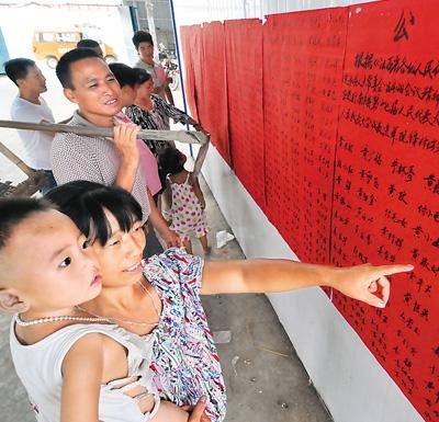 江西南丰县傅坊乡梅林村选民观看张榜公布的选民名单。 黎兴旺摄(人民图片)