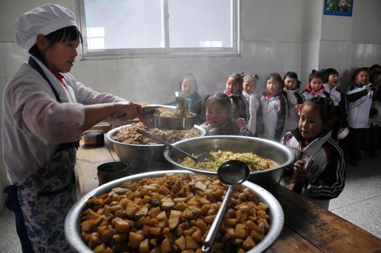 2012年12月17日,重庆巫山县,在农村学校食堂打饭的小学生。/视觉中国