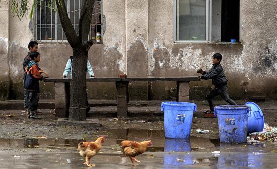 2015年9月13日,四川凉山,孩子们用砖头和木板打乒乓球。/视觉中国